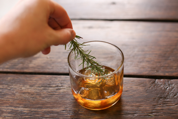 stirring your drink with a rosemary sprig