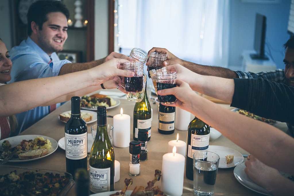 Toasting with wine at a friends Thanksgiving (Friendsgiving) celebration