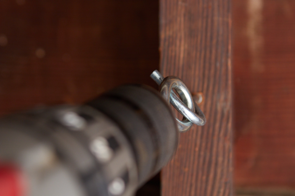 drill using a hook eye to turn a screw hook