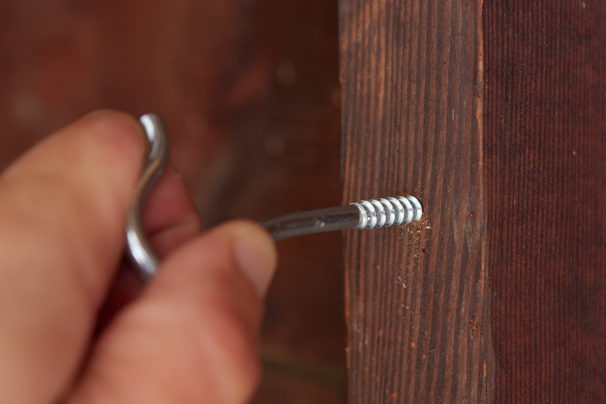 screw hook being inserted into pilot hole