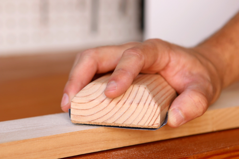 using a sanding block to sand wood