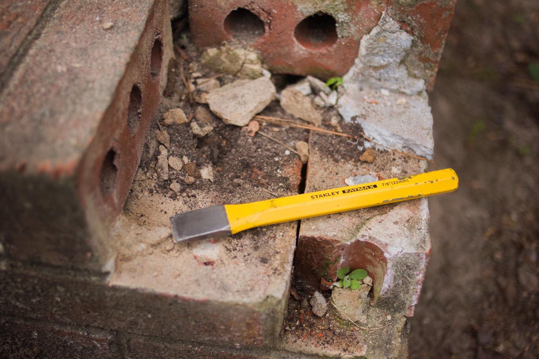 chisel clearing away damaged mortar and bricks