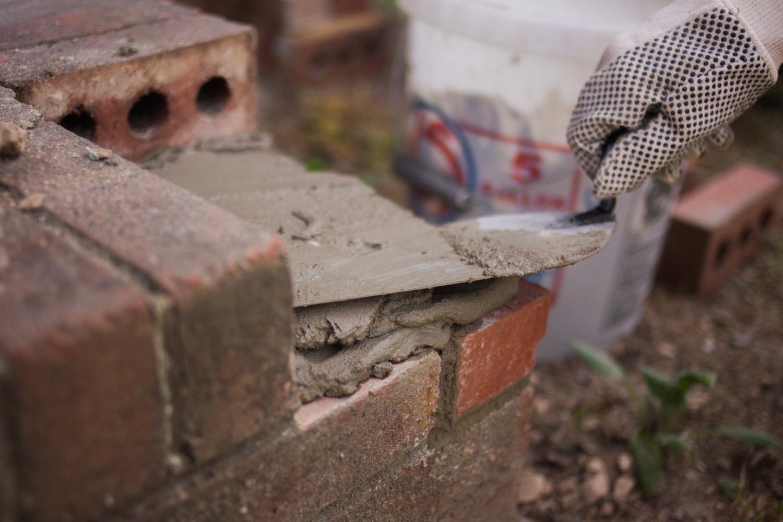 applying mortar to bricks