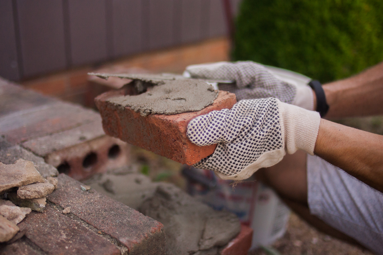 spreading mortar onto bricks