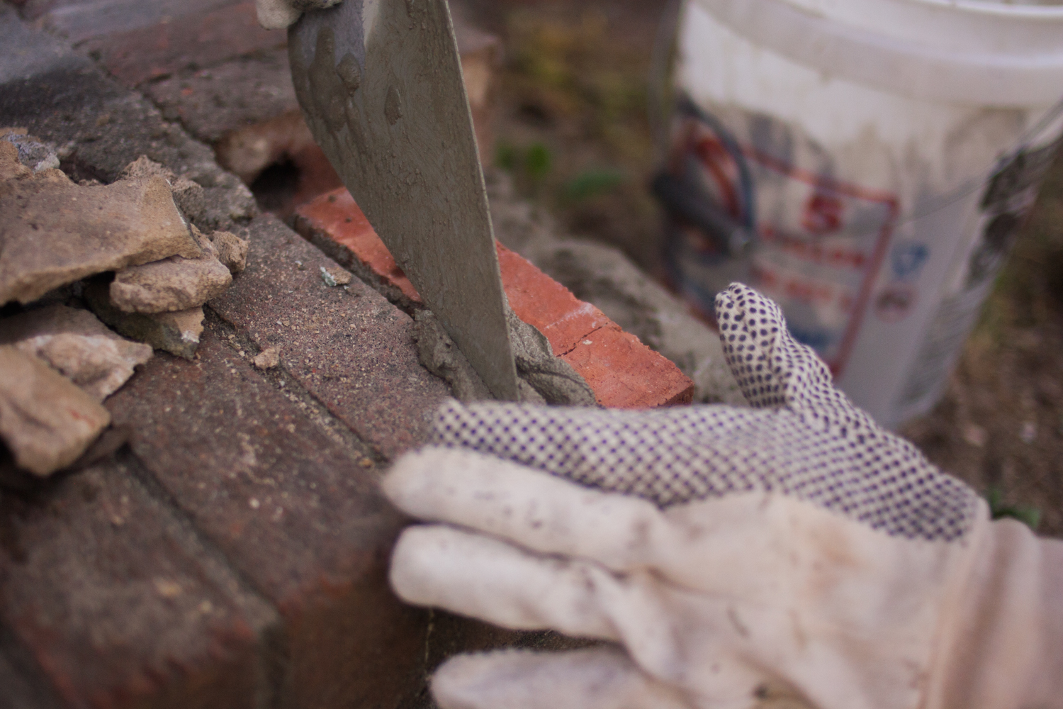 wiping excess mortar from in-between bricks