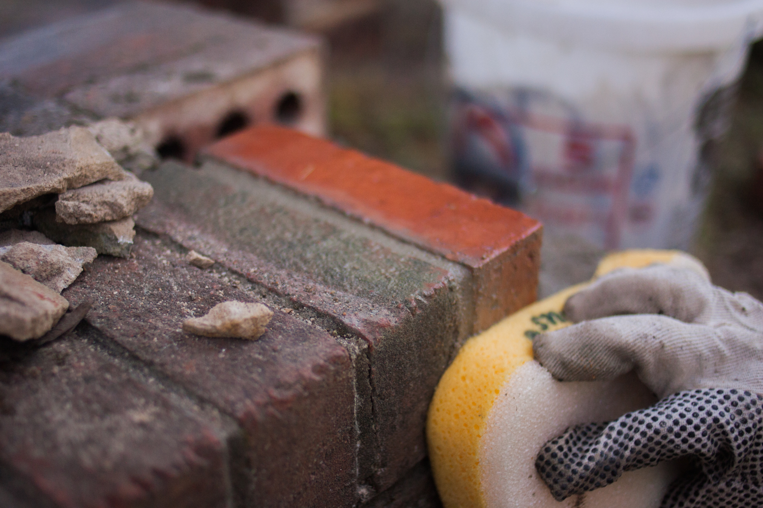 wiping excess mortar away from brick face with a grout sponge
